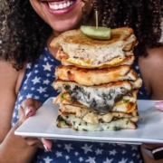 smiling-woman-holding-stack-of-grilled-cheese-sandwiches